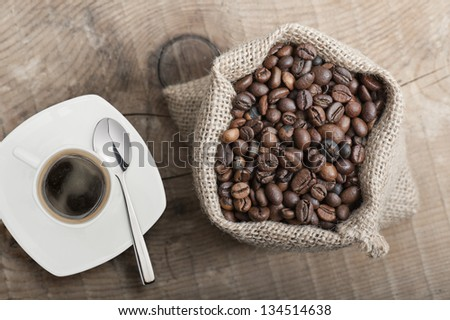 coffee beans in jute bag on wooden table with cup of coffee