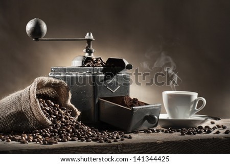 coffee beans in jute bag with coffee grinder and hot cup of coffee on wooden table