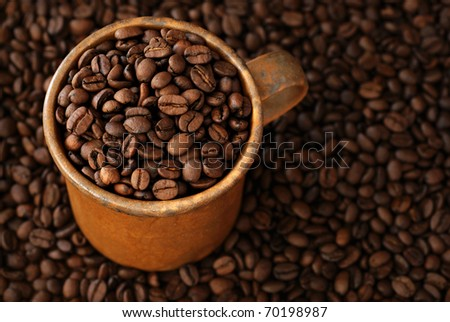 Coffee beans in rustic stoneware mug with coffee bean background.  Macro with shallow dof.