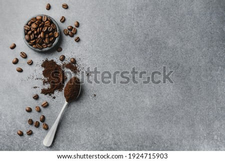 Coffee beans in small bowl with coffee in spoon. View from above. Coffee concept.