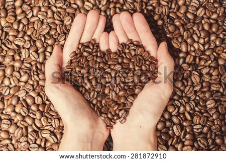 Coffee beans in the hands of heart shaped