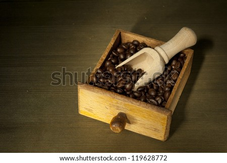 coffee beans in tray and wooden spoon, wooden table background