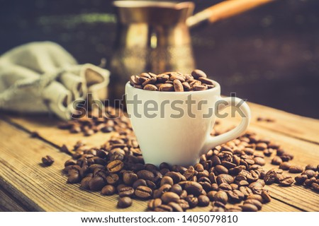 Coffee beans in white cup on the rustic wooden background. Selective focus. Shallow depth of field.