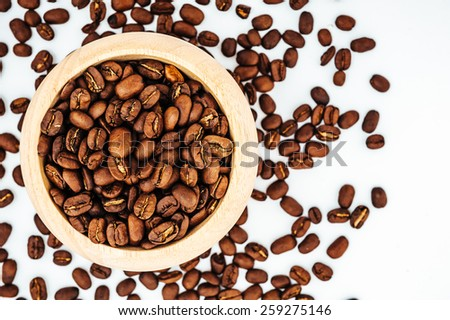 Coffee beans in wooden bamboo mortar isolated on white background. coffee beans isolated on white background.