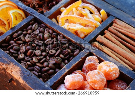 Coffee beans, kumquats, cinnamon, candied peels, dried orange slices and star anise in rusty wooden crate