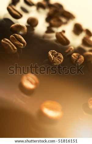 Coffee beans lying on a shiny glass surface.