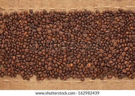 Coffee beans lying on sackcloth between the two lines #162982439