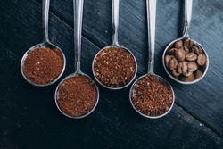 Coffee beans of different degrees of roasting and grinding are scattered in metal spoons. Texture background.