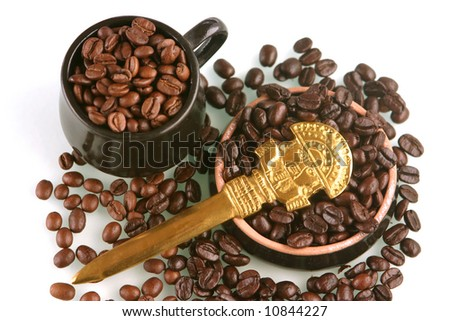 Coffee beans of two kind in a little brown cup and saucer with gold ritual knife from Peru