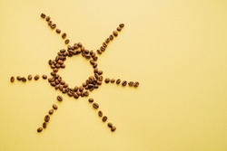 Coffee beans on a yellow background in the form of the sun. Caffeine morning drink. Closeup of bean grains.
