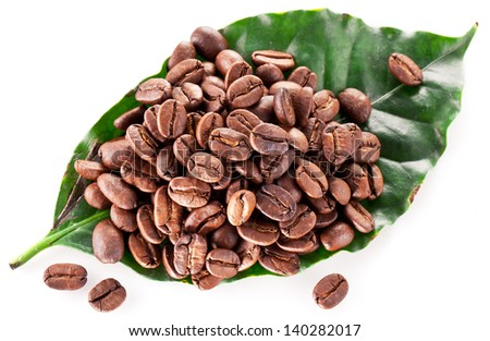 Coffee beans on leaf. Closeup snapshot on a white background.