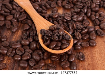 Coffee beans on wood spoon, isolated on wooden board