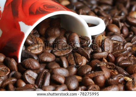 coffee beans pouring out of a coffee cup
