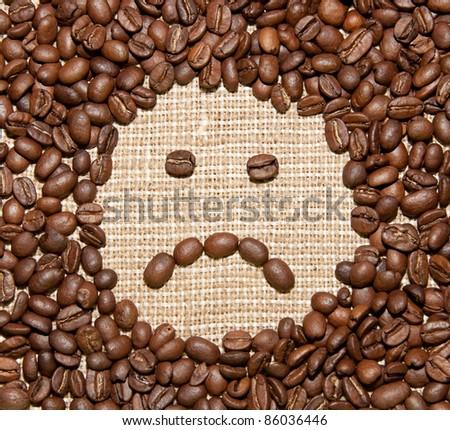 coffee beans sad smile on burlap background