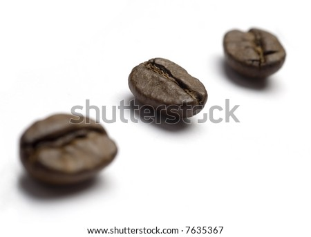 Coffee beans spilled onto a white background. Closeup of whole beans isolated on white. - stock photo