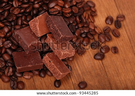 Coffee beans spilled out of the bag with some pieces of aerated chocolate over wooden background/coffee beans with some kinds of chocolate