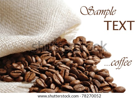 Coffee beans spilling from burlap sack on white background with copy space.  Macro with shallow dof.