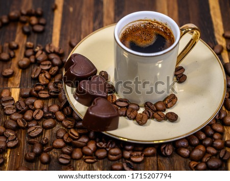 Coffee beans wallpaper. Dark brown roasted coffee bean background with mini heart-shaped chocolate and a cup of dark coffee. Focus on chocolate. Valentine's day celebration idea concept. Side view.