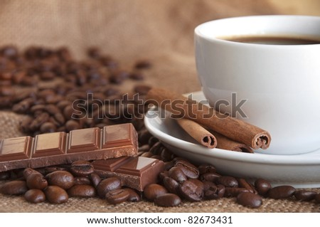 Coffee beans with cinnamon sticks and cup of coffee
