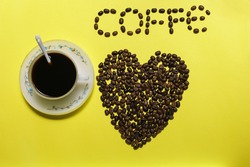 Coffee beans with classic old vintage cup of organic black liquid