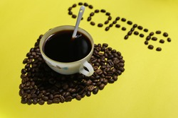 Coffee beans with classic old vintage cup of organic black liquid cof