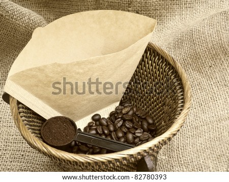 Coffee beans with filter and scoop in wicker basket on burlap background