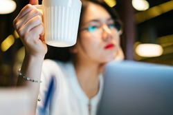 Coffee break - asian office woman holding a cup of coffee working overtime infront of computer at night.
