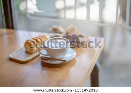 Coffee break at cafe,selective focus cup of coffee blurred bread on table in cafe,selective focus. #1131492818