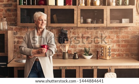 Coffee break. Calm senior lady standing at kitchen, drinking coffee and looking at empty space, panorama