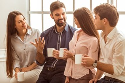Coffee break chat. Group of attractive business people, standing next to each other, holding a cups, smiling standing at the window