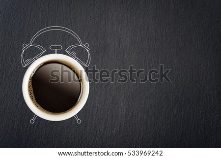 Coffee break concept. Coffee cup and sketch of alarm clock on black slate background.