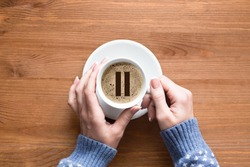 Coffee break. Female hands in sleeves of cozy blue pullover touches white cup of classic coffee, top view, close up. Pause icon on foam. Pause, hygge, relaxing, home, cosiness, warmth, breakfest and