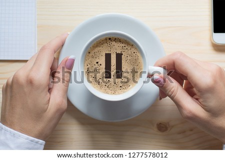 Coffee break. Female hands touches white cup of classic coffee, top view, close up. Pause icon on foam. Pause, break, short breather, relax, pit stop in the middle of business life. #1277578012