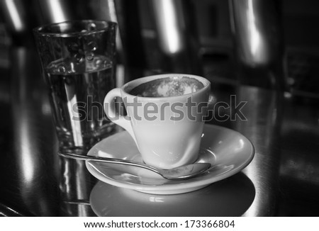 Coffee break is over.  Empty coffee cup and glass of water on the shiny counter of the typical Parisian bar. Aged photo. Black and white.