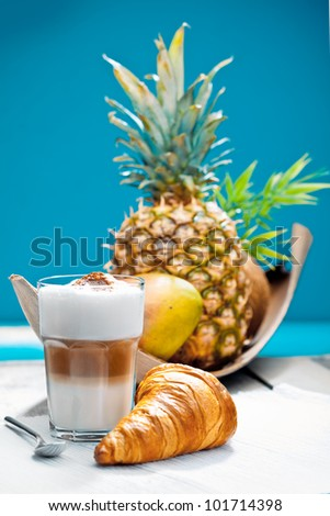Coffee Break on a deck at the beach with a croissant and tropical fruits as a breakfast.