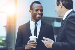 Coffee break. Two cheerful business men talking while one of them holding coffee cup