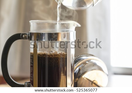 Coffee brewing in a French press in warm morning light;