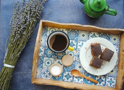 Coffee, cake and flowers: Cup of Turkish coffee in a yellow enamel mug served on the wooden tray with azulejo motif, chocolate cake and lavender bunch. Top view.