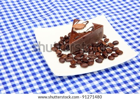 Coffee cake with whole coffee bean decoration on picnic table cloth background