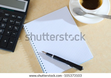 coffee, calculator and notebook on the desk