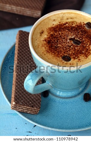 coffee cappuccino in a  blue ceramic cup and chocolate wafers