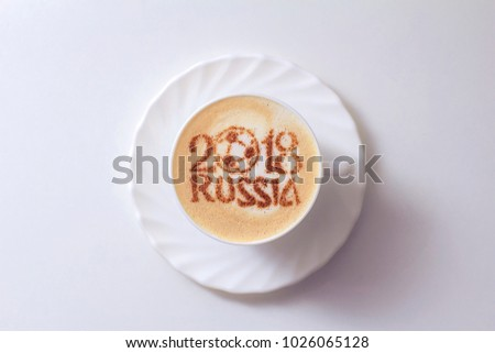 Coffee cappuccino in a white cup with a pattern of russia 2018 from cinnamon #1026065128