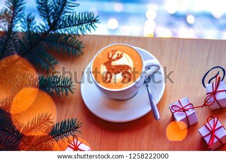 coffee cappuccino with cinnamon Christmas deer pattern on milk foam