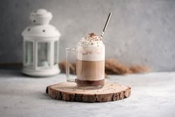 Coffee cocktail mocha with whipped cream on a wooden tray on a stone gray background. Delicious homemade sweet dessert of coffee with milk and cocoad.