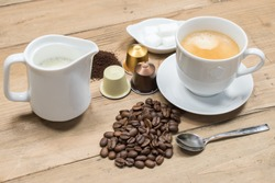 Coffee concept: Creamy cup of coffee, coffee beans, jug of milk, machine capsules and sugar cubes on wooden background.