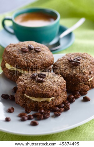 Coffee cookies cream filled served on the oval plate with cup and scattered coffee beans,shallow focus