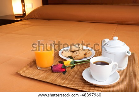 Coffee, cookies, orange juice and a pair of roses over the bed for a romantic breakfast in an orange predominant image.