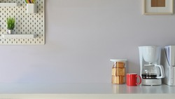 Coffee corner table in office with coffee machine, mug, snack, peg board on white table.