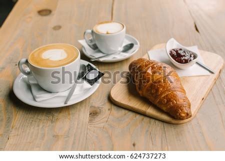 Coffee, Croissant and jam on a wooden table #624737273