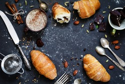 Coffee, croissants, chocolate, spices, nuts and vintage cutlery. Flat lay composition of sweet breakfast food on dark stone background with copy space for text. Table top view
